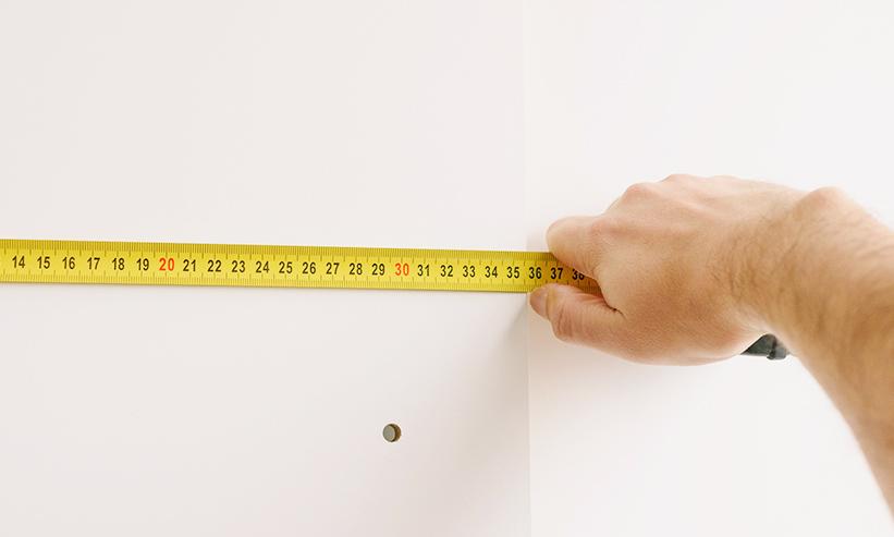 スケールを持ち壁を測る男性