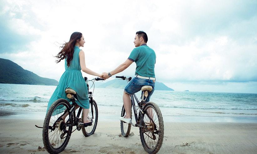 自転車にまたがり手を繋ぐカップル