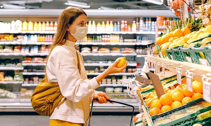 スーパーでフルーツを手に取る女性