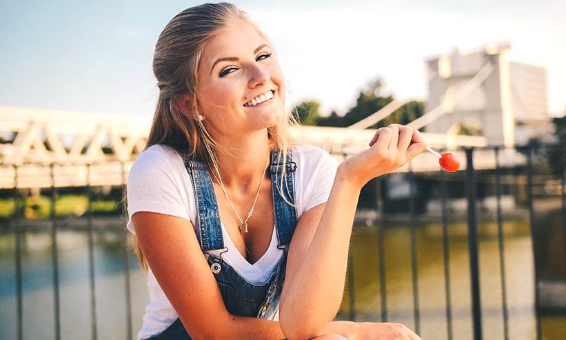 飴を持っている笑顔の女性