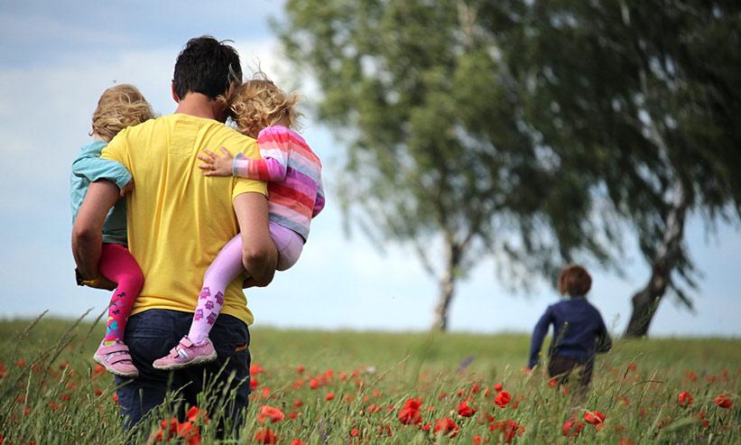2人の子供を抱えて歩く男性