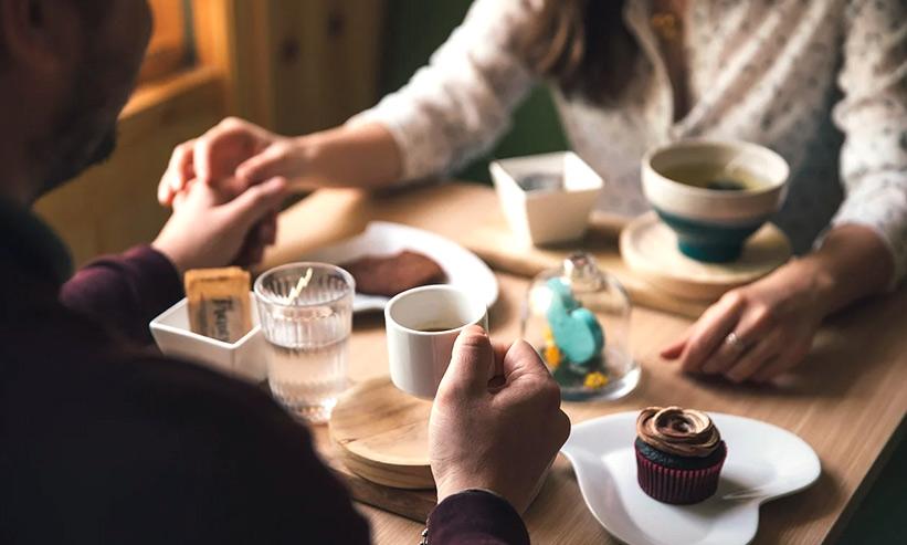 カフェでコーヒーを飲みながら手を繋いでいるカップル