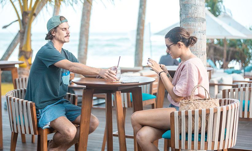 カフェで女性に飲み物を差し出す男性