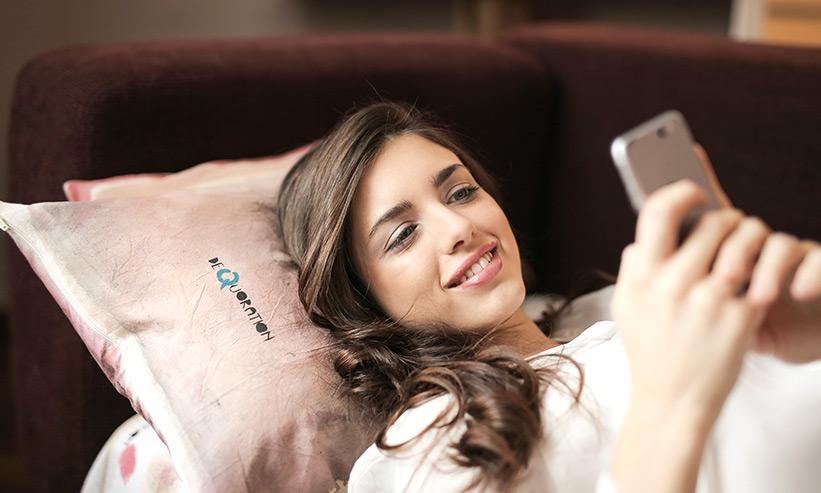 寝転んでスマートフォンを操作する女性