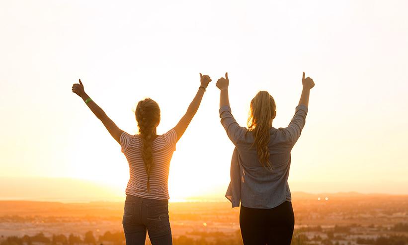 夕陽に向かって手をあげる2人の女性