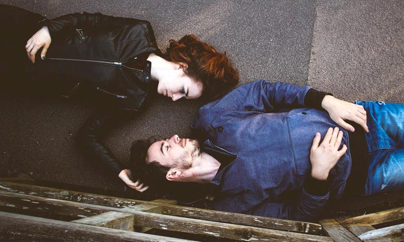 寝転んで見つめ合うカップル