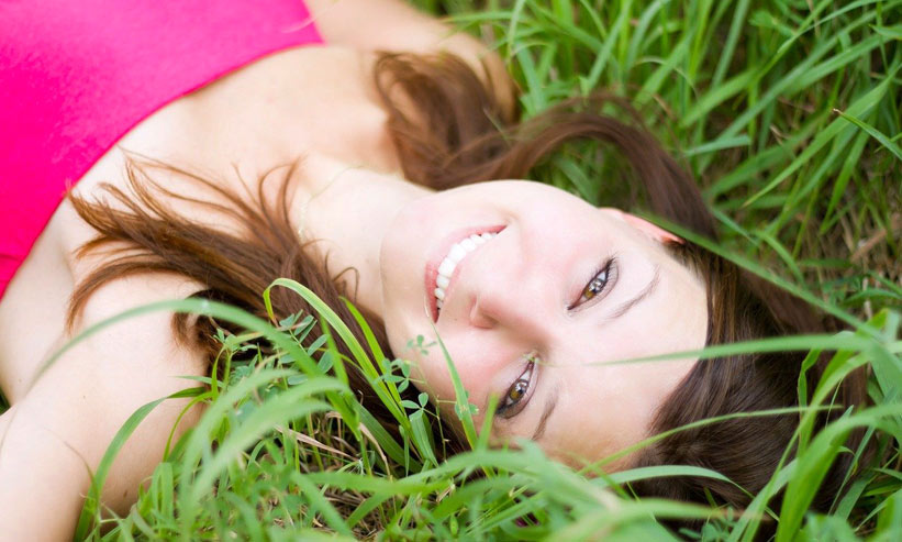 草むらで寝転んでいる女性