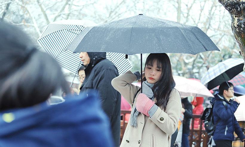 人混みの中傘をさす女性