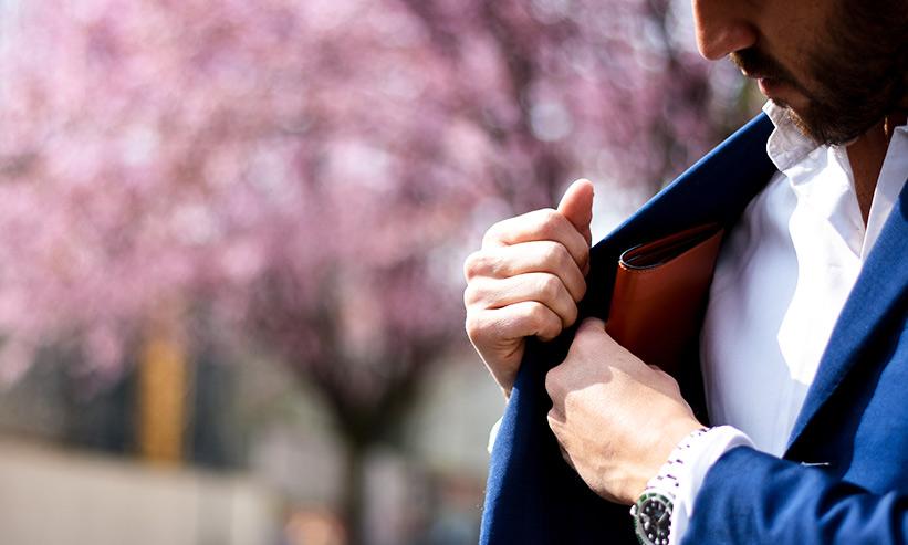 財布をジャケットにしまう男性