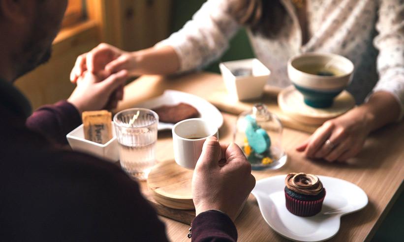 カフェでコーヒーを飲んでいるカップル