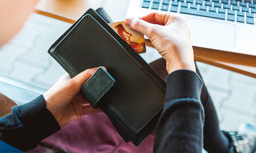 財布にカードをしまう女性