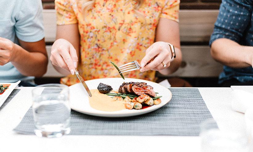 フォークとナイフで食事をする女性
