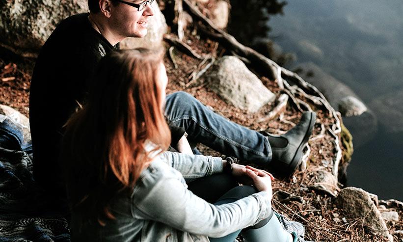 水辺で話をしているカップル
