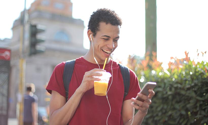 笑いながらスマートフォンを見る男性