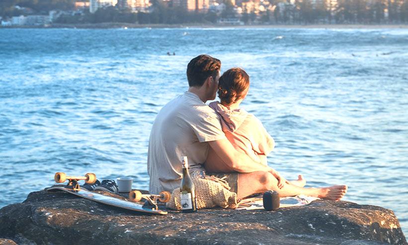 座って女性を後ろから抱きしめる男性