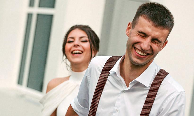 笑いながら女性の手を引く男性
