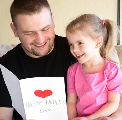子供と一緒にメッセージカードを見る男性