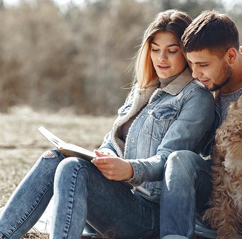 男性にもたれ掛かり一緒に本を読む女性