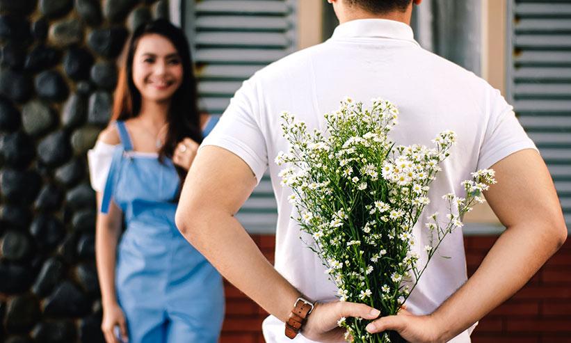 花束を隠し女性を驚かせようとしている男性