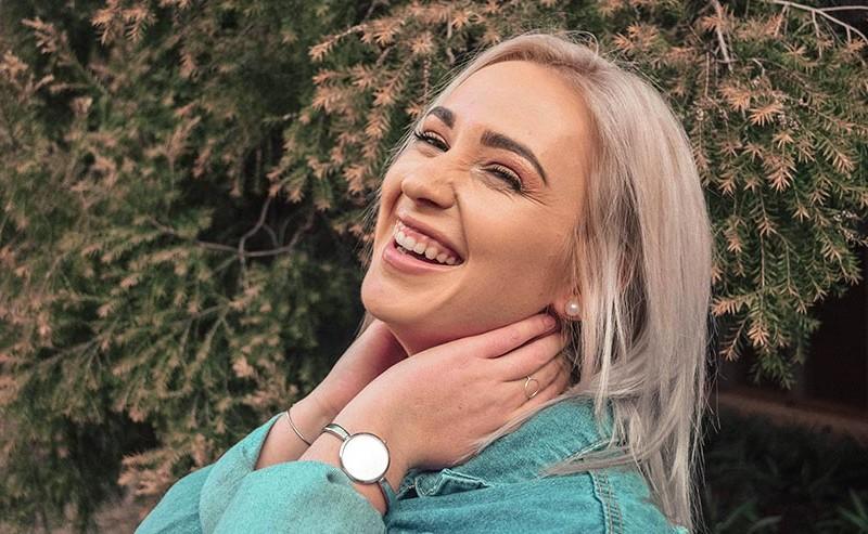 首に手をあて笑っている女性