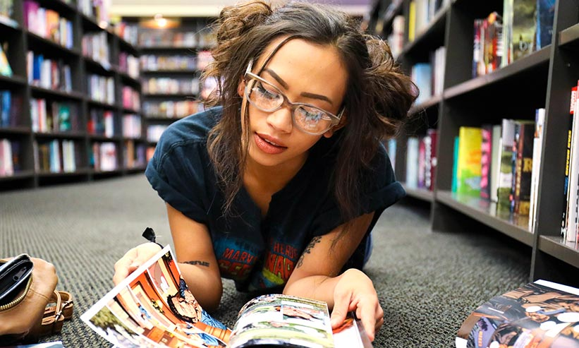 寝そべって本を読んでいる女性