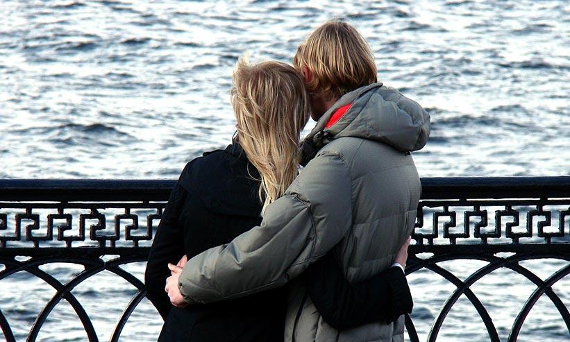 寄り添い海を眺めるカップル