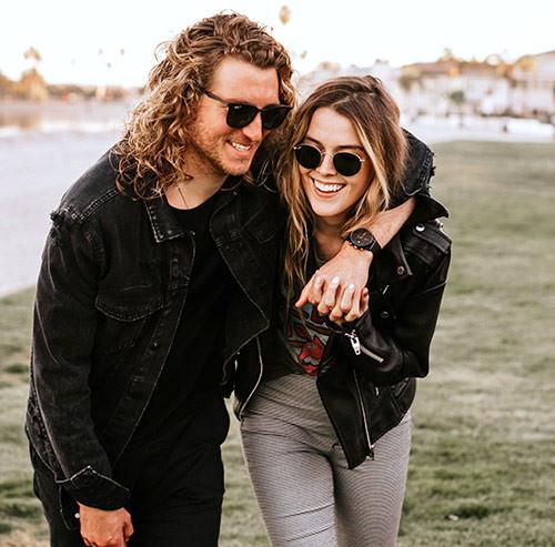 笑いながら肩を組むカップル