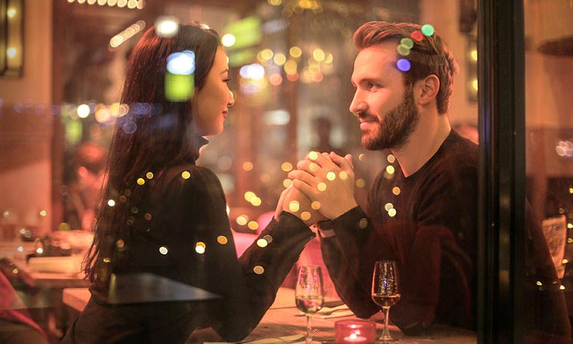 見つめあいながらお互いの手を握るカップル