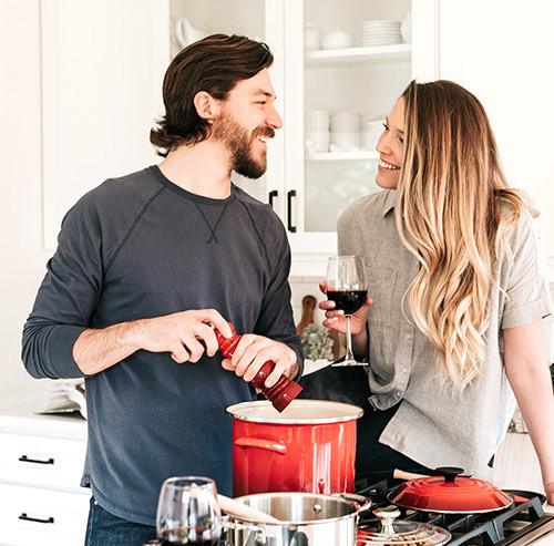 キッチンで笑いながら料理をするカップル