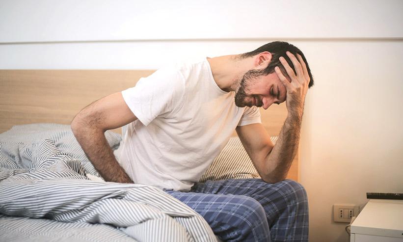 頭を抱え悩む男性