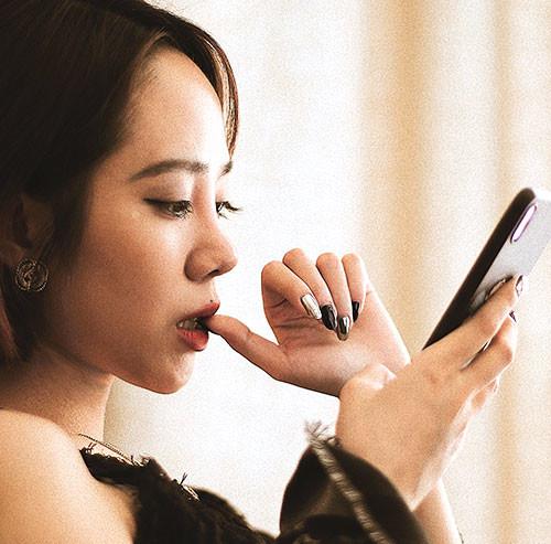 指を咥えスマートフォンを操作する女性