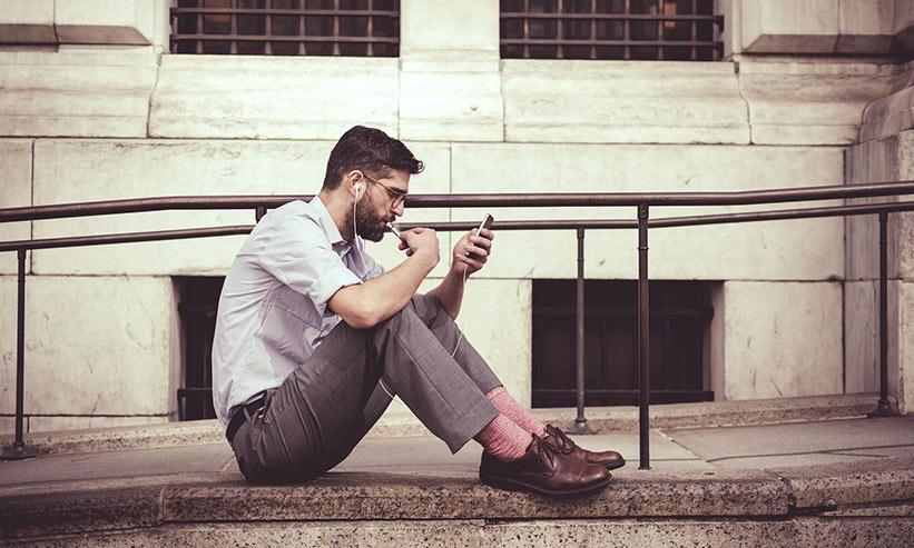 座ってスマートフォンをじっと見つめる男性
