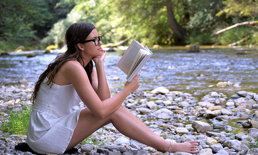 河原で本を読んでいる女性