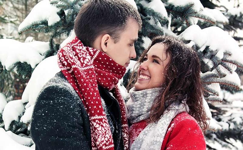 雪が降る中見つめ合うカップル