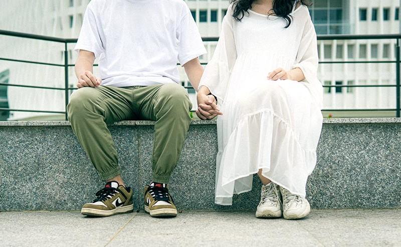 手を繋いで座るカップル