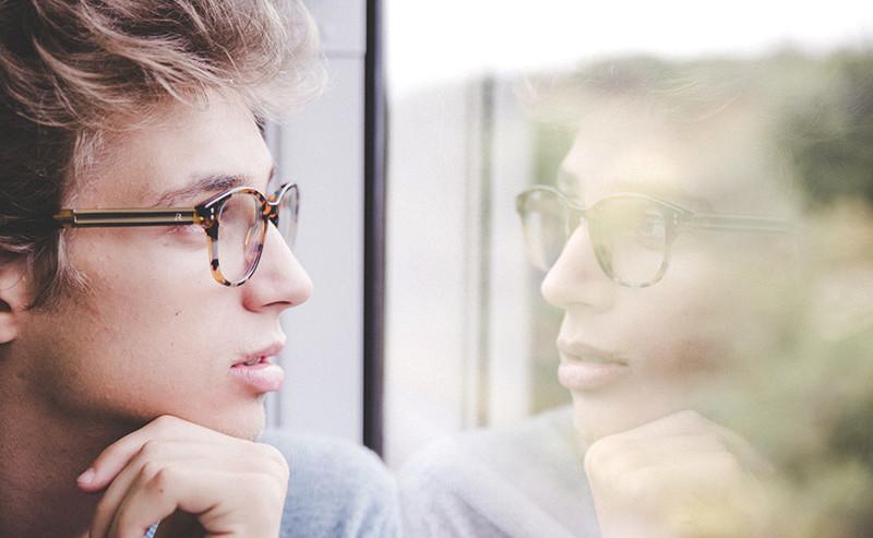 窓の外を見つめる男性
