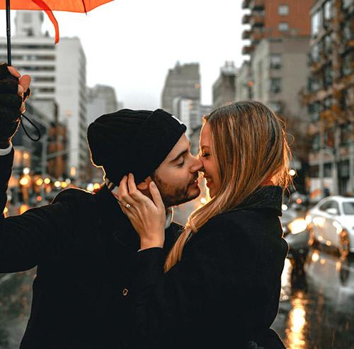 傘をさしながらキスをするカップル