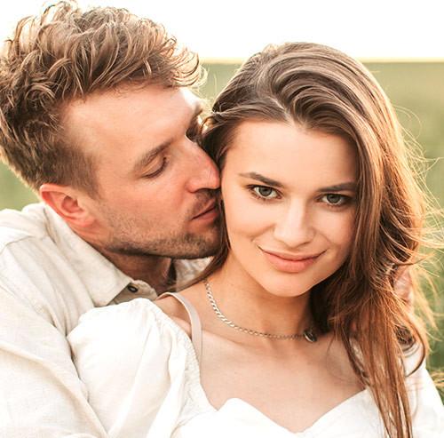 女性の頬にキスをする男性
