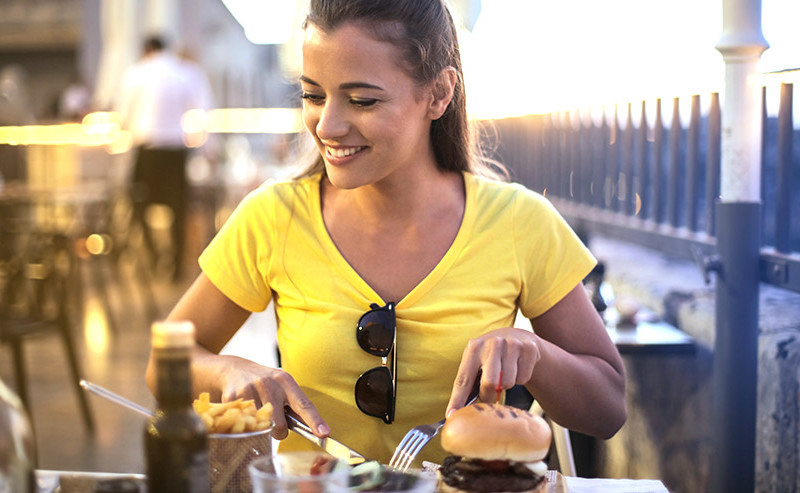 ハンバーガーを食べている女性