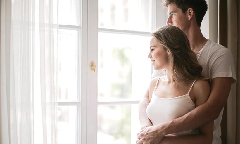 寄り添い窓の外を眺めるカップル