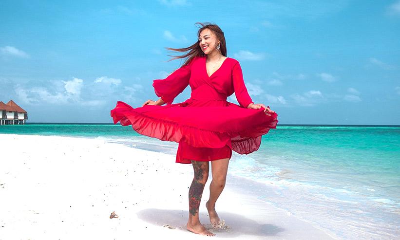 ビーチで踊る赤いドレスの女性