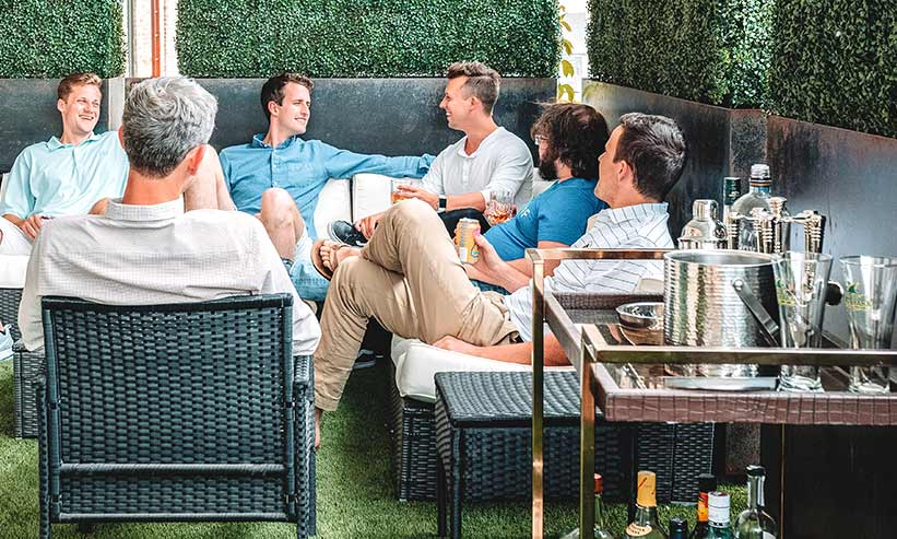 ソファに座り雑談する複数の男性