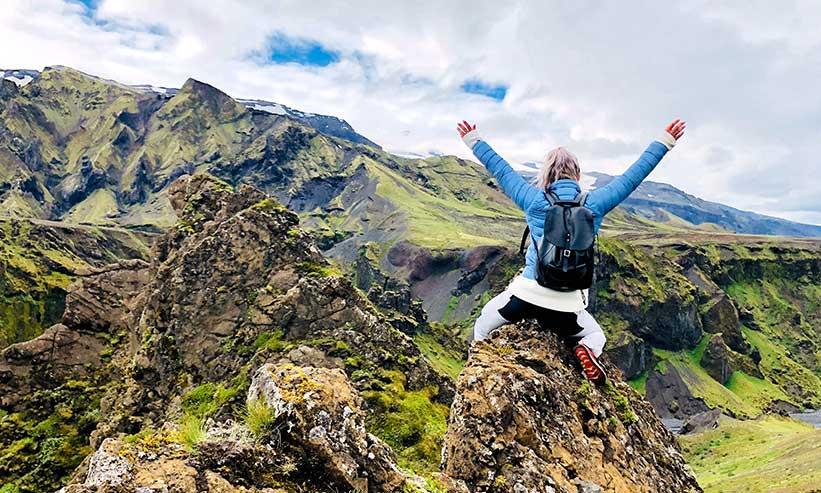 山に登り両手を大きく上にあげる女性