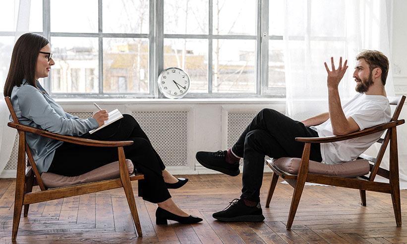 椅子に向き合って座り話をするカップル
