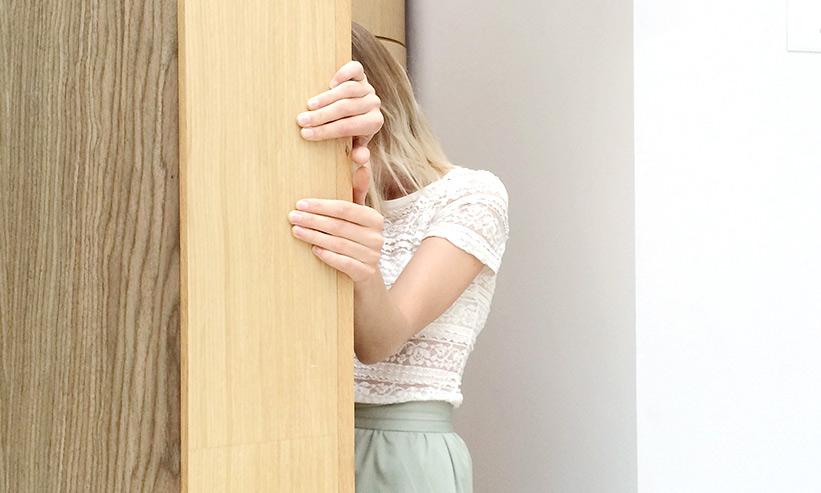 壁に隠れる女性