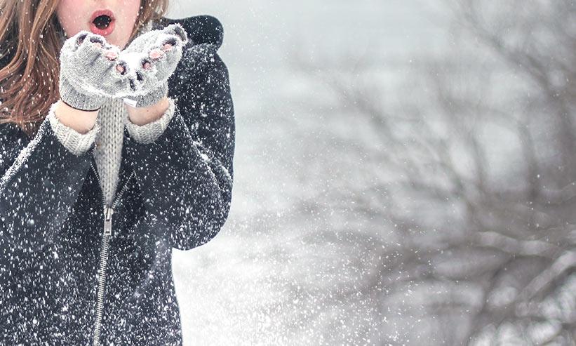 ふぅーっと息をかけて雪を飛ばす女性
