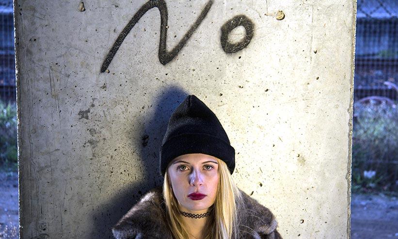 Noと書かれた壁の前に立つ女性