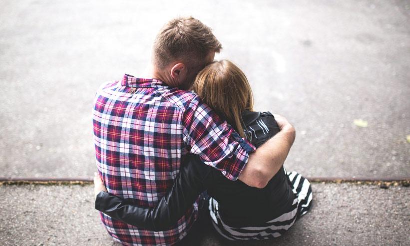 お互いに抱きしめ合うカップルの後ろ姿