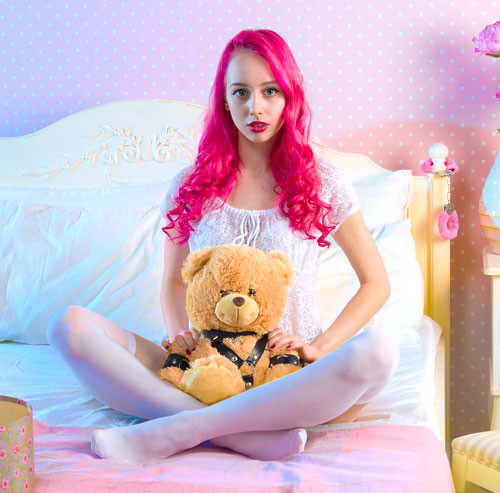 ぬいぐるみを持ちベッドに座っている女性