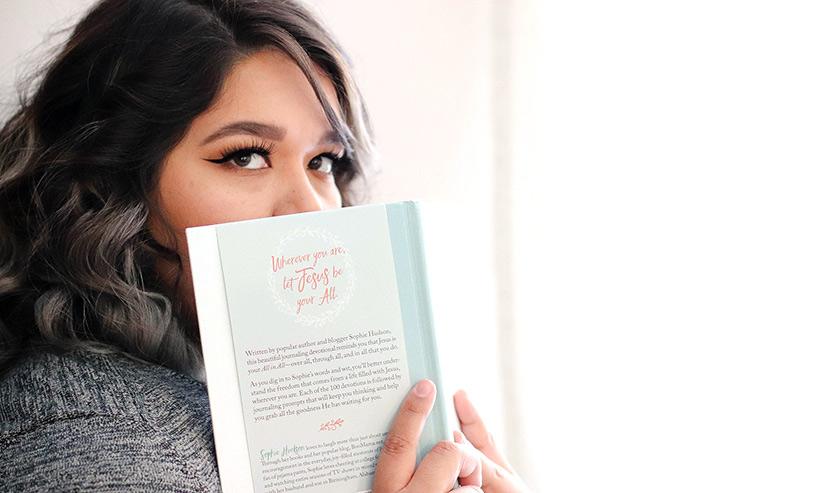 本で口元を隠す女性
